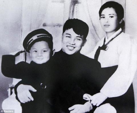 A young salute: A picture of North Korean founder Kim Il Sung, his first wife, Kim Jong-suk, and his son, Kim Jong Il, is displayed at the Unification Hall at the West Seoul Life Science High School in Seoul