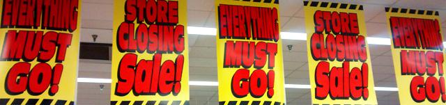 Liquidation banners hang from the ceiling of a Kmart store in Oregon City, Ore.
